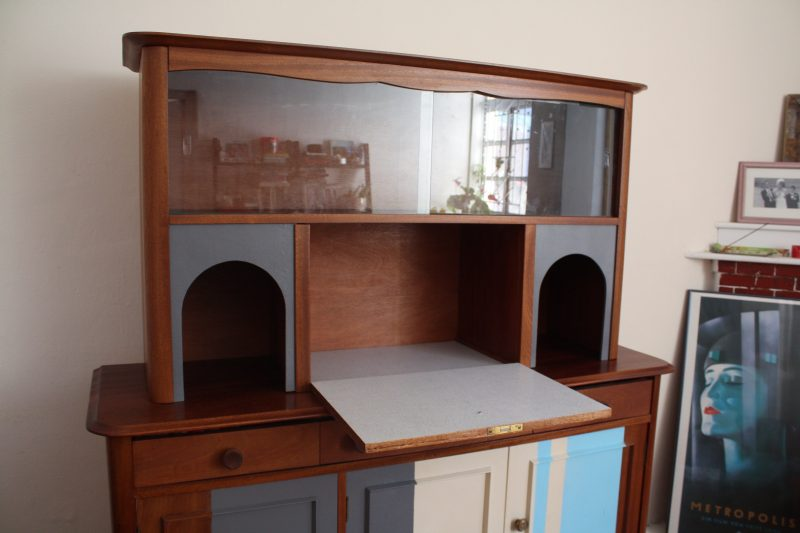 drop down drinks cupboard with arched trmings on either side